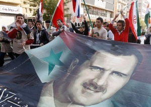 Pro-Syrian regime protesters shout slogans and carry a huge portrait of the Syrian president Bashar Assad during a protest against the Arab League decisions, in Damascus, Syria, on Friday Nov. 25, 2011. Syria missed an Arab League deadline Friday to allow hundreds of observers into the country, prompting the bloc to consider economic sanctions against Damascus for its eight-month crackdown on dissent, a senior diplomat said. (AP Photo/Muzaffar Salman)